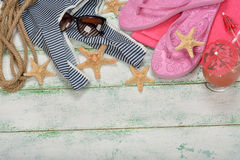 Beach sandals, towels, glasses on a wooden background Stock Images