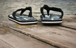 Beach. Sandals on wooden pier by lake Royalty Free Stock Images