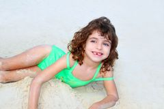Beach sandy girl smiling little children. Green swimming suit royalty free stock photography