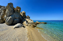 Beach. Sandy beach and rocks of unusual shape in morning sunlight under clear, blue sky, Fava beach, Chalkidiki, Sithonia, Greece Royalty Free Stock Images