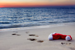 The beach with Santa Claus hat at sunset. Human footprints on a sandy beach with Santa Claus hat at sunset Royalty Free Stock Photo
