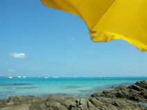 Beach in Sardinia. Sardinia sea with portion of bright yellow beach umbrella (Stintino beach Royalty Free Stock Photography