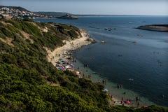 Beach in Sardinia, Italy. Beautiful beach of limestone rock S`Archittu di Santa Caterina, Oristano Province, Sardinia, Italy. Lot of people and beach umbrellas stock image