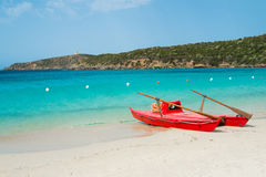 Beach in Sardinia. Red rowboat on Tuerredda beach along the coast of Teulada, South Sardinia, Italy Royalty Free Stock Photos