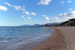 Beach of Sardinia. Spiaggia della Sardegna. Sardinia, blue sky, people in the distance Stock Photo