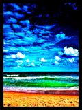 The beach in saturated colors. A beach overprocessed, turquoise waters, golden sand, shoreline, blue skies Royalty Free Stock Photo