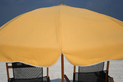 Beach scene. Closeup of a beach umbrella and chairs Royalty Free Stock Images