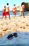 Beach scene. With sun glasses on the towel and people walking in the background Royalty Free Stock Photography