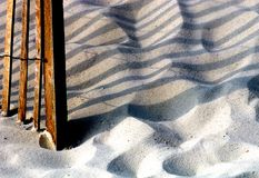 Beach Scene. Image of wooden fence on the beach with shadow Royalty Free Stock Image