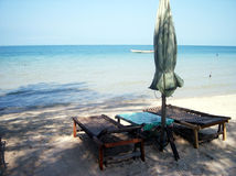 Beach scene. 2 laying chairs and a table near the beach royalty free stock photography