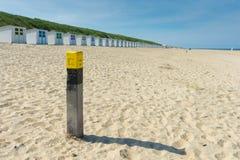 Beach scene with beach pole and beach houses Royalty Free Stock Image