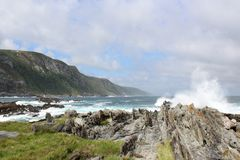 Beach Scene. The beautiful beach with gray rocks, green mountains, and ocean spray and blue sky in Tsitsikamma Nature Reserve, South Africa Stock Images