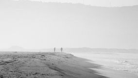 Beach scene in black and white with mist and people Stock Photography