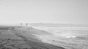 Beach scene in black and white with mist and people Stock Photo