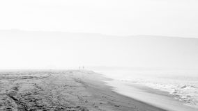 Beach scene in black and white with mist and people Royalty Free Stock Photos