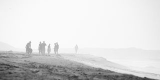 Beach scene in black and white with mist and people, grain is in Stock Images
