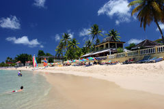 Beach scene in Caribbean. Swimmers on beach on island of St. Lucia Stock Photo