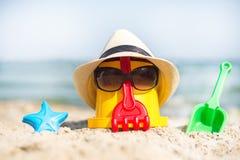 Beach scene with children toys. The Beach scene with bucket and sunglasses Stock Photo