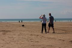 Beach scene with a couple walking August 2018 royalty free stock photography