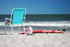 Beach scene of empty chair and surf board Stock Image