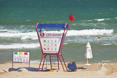 Beach scene with lifeguard. Lifeguard relaxing on the beach Royalty Free Stock Image