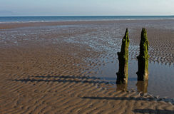 Beach Scene, near Silloth, Cumbria, Lake District. Wooden beach posts, near Silloth Cumbria, Lake District, England. Coast of Scotland in the distance Stock Photos
