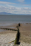Beach Scene, near Silloth, Cumbria, Lake District. Wooden beach posts, near Silloth Cumbria, Lake District, England. Coast of Scotland in the distance Royalty Free Stock Image