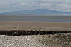 Beach Scene, near Silloth, Cumbria, Lake District. Wooden beach posts, near Silloth Cumbria, Lake District, England. Coast of Scotland in the distance Royalty Free Stock Photo