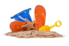 Beach scene with pail, flip-flops, starfish,shovel. Beach scene with blue pail, orange flip-flops, starfish and a yellow shovel royalty free stock image