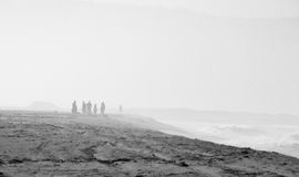 Beach scene with people walking in black and white with mist Royalty Free Stock Photos