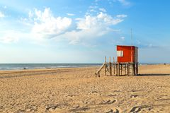 Beach scene. Red lifeguard tower in foreground. Atlantic coast. Mar de las Pampas. Argentina. Mar de las Pampas. Argentina. Beach scene. Red lifeguard tower in royalty free stock photos