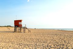 Beach scene. Red lifeguard tower in foreground. Atlantic coast. Mar de las Pampas. Argentina. Mar de las Pampas. Argentina. Beach scene. Red lifeguard tower in stock photo