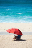 Beach Scene with Red Umbrella and Blue Water Stock Images