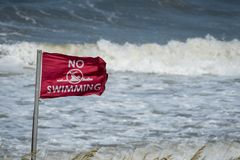 Closeup of red flag and pounding surf Royalty Free Stock Photography