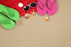 Beach scene in summer on vacation with sand, sunglasses, towel a Royalty Free Stock Image