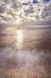 Beach scene with sun beams in the horizon Stock Photo