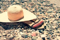 Beach scene. Sun straw hat and flip flop sandals lying on on sea pebble beach royalty free stock images