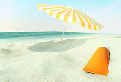Beach scene with sunscreen and sun umbrella against ocean. Royalty Free Stock Images