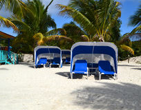 Tropical Beach Cabana and lounge Chairs. To empty chairs near the ocean waiting for a couple to enjoy them Royalty Free Stock Photography