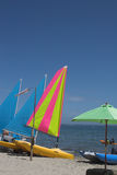 Beach scene with yachts and canoe. Beach scene with yachts,umbrella and canoe in water Stock Photos