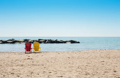 Beach scene with two colorful adirondack chairs Royalty Free Stock Photography