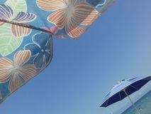 Umbrella with floral pattern. Beach scenery with sea and sky visable from under umbrella with floral pattern Royalty Free Stock Image