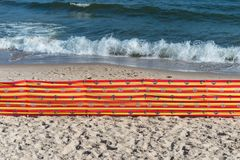 Beach screen on the Polish beach on a sunny summer day in the background a rough sea. Beach screen on the Polish beach on a sunny summer day in the background a Stock Photography