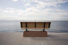 Beach at sea. Empty bench standing on a walkway looking at sea horizontal shot Royalty Free Stock Photos