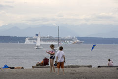 Beach sea cruise ship. People were relaxing at Golden Gardens Seattle on a Sunday afternoon. A NCL cruise ship was going north. Most likely it is going to Alaska Stock Photography