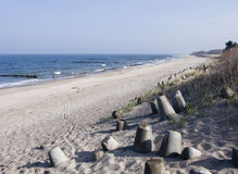 Beach,sea and dunes. A calm landscape of a wide beach, sea (ocean) and sand dunes strengthened by concrete blocks Royalty Free Stock Image
