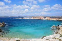 Beach and sea at Paradise Bay, Malta. Rocky coastline with hotels and ferry terminal to the rear, Paradise Bay, Malta, Europe Stock Photos