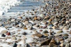 Beach, sea pebbles. Surf, colored pebbles, sea foam Stock Images