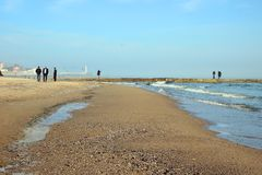 Beach by the sea and people strolling leisurely Royalty Free Stock Images