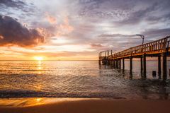 Beach, sea and pontoon at sunset Royalty Free Stock Photo